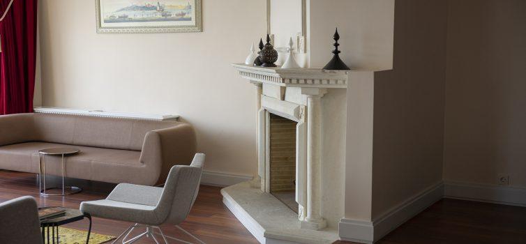 Дровяной угловой камин в интерьере гостиной