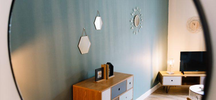 Зеркало над комодом в интерьере гостиной