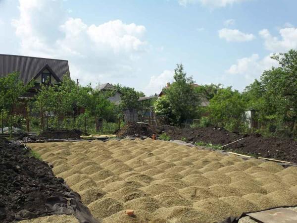 Слой песка обязательно послойно утрамбовывается специальной виброплитой