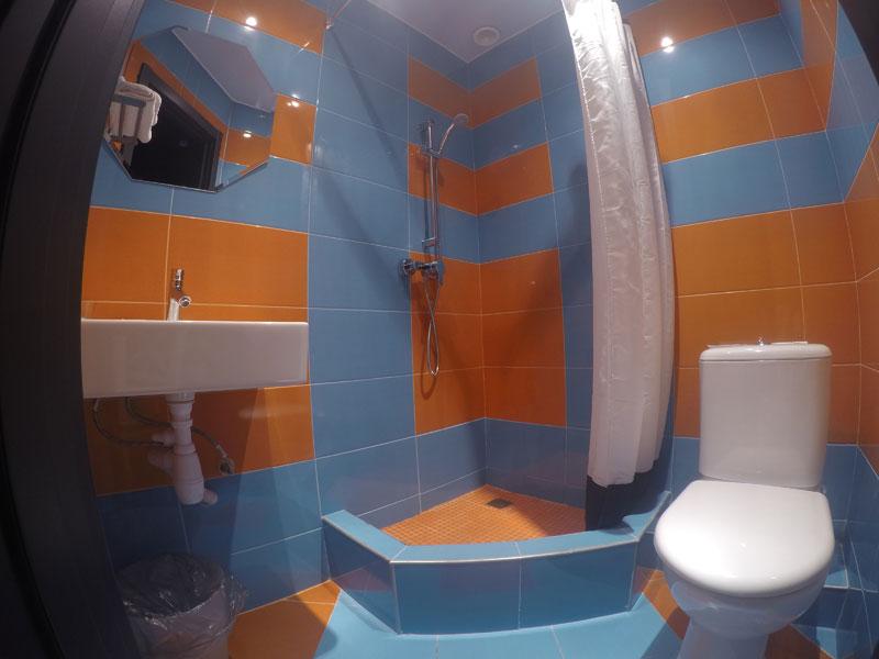 Интерьер небольшой ванной комнаты в голубом и оранжевом цвете